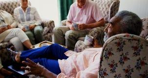 Vista lateral del hombre mayor afroamericano activo que obra recíprocamente con los amigos mayores en la clínica de reposo almacen de video