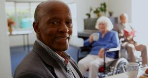 Vista lateral del hombre mayor afroamericano que sonríe en la clínica de reposo 4k almacen de video