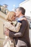 Vista lateral del hombre que abraza a la mujer feliz afuera Fotos de archivo libres de regalías