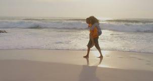 Vista lateral del hombre que da paseo del transporte por ferrocarril a la mujer en la playa 4k metrajes
