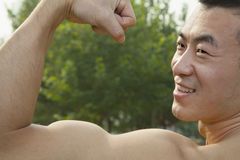 Vista lateral del hombre sonriente muscular que muestra apagado y que dobla su bíceps Foto de archivo libre de regalías