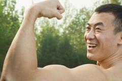 Vista lateral del hombre sonriente muscular que muestra apagado y que dobla su bíceps Fotos de archivo libres de regalías