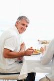 Vista lateral del hombre sonriente que cena Imágenes de archivo libres de regalías