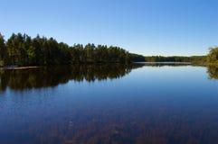 Vista lateral del lago con el cielo azul claro Fotos de archivo