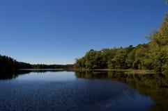 Vista lateral del lago con el cielo azul claro Imagenes de archivo