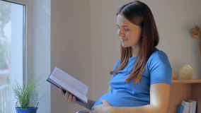 Vista lateral del libro de lectura sorprendido de la mujer embarazada mientras que se sienta en el sofá almacen de video