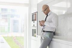 Vista lateral del mediados de hombre de negocios adulto usando el teléfono celular en casa Imagen de archivo