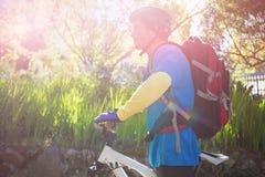 Vista lateral del motorista masculino de la montaña con la bicicleta en bosque Imagen de archivo