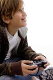 Vista lateral del muchacho alegre que disfruta del juego de video fotografía de archivo libre de regalías