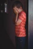 Vista lateral del muchacho que cubre su cara con las manos mientras que se coloca en pasillo Imágenes de archivo libres de regalías