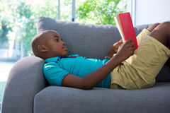 Vista lateral del muchacho que miente mientras que lee la novela en el sofá en casa imagen de archivo