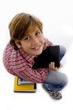 Vista lateral del muchacho que se sienta en la pila de libros Imágenes de archivo libres de regalías