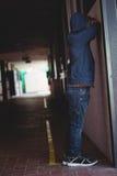 Vista lateral del muchacho triste que se inclina en la pared en pasillo Fotos de archivo