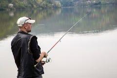 Vista lateral del pescador Reeling String And que lanza a Rod In The Calm Lake Imagen de archivo