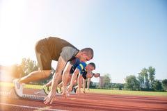 Vista lateral del primer de la gente cosechada lista para competir con en campo de la pista Fotografía de archivo libre de regalías