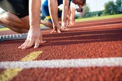Vista lateral del primer de la gente cosechada lista para competir con en campo de la pista Foto de archivo libre de regalías