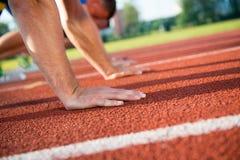 Vista lateral del primer de la gente cosechada lista para competir con en campo de la pista Fotografía de archivo