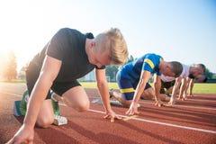 Vista lateral del primer de la gente cosechada lista para competir con en campo de la pista Imagen de archivo libre de regalías