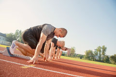 Vista lateral del primer de la gente cosechada lista para competir con en campo de la pista Imagen de archivo