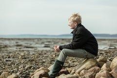 Vista lateral del solo muchacho rubio que se sienta en la playa Foto de archivo libre de regalías