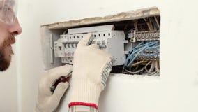 Vista lateral del técnico que trabaja y que repara la caja eléctrica almacen de video