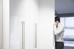 Vista lateral del teléfono móvil de Hiding And Using del hombre de negocios imágenes de archivo libres de regalías