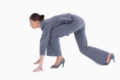 Vista lateral del tradeswoman en la posición sprinting imagen de archivo