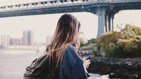 Vista lateral del turista femenino joven con la mochila que camina a lo largo del río soleado de Brooklyn Park usando la cámara l metrajes