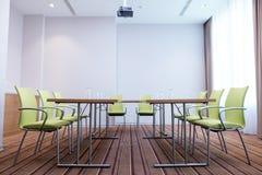 A vista lateral disparou da tabela com vidros vazios e chaires modernos do escritório do verde Fotos de Stock Royalty Free