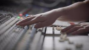 A vista lateral disparou de um músico que trabalha no console de mistura audio em um estúdio da música vídeos de arquivo