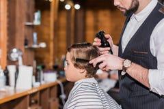 vista lateral do cabelo de penteado e de pulverização do barbeiro de foto de stock royalty free