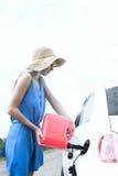 Vista lateral do carro do reabastecimento da mulher na estrada secundária Imagens de Stock