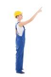 Vista lateral do construtor da jovem mulher que aponta em algo isolado Imagem de Stock
