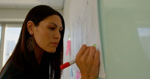 Vista lateral do executivo fêmea caucasiano novo com a tabuleta digital que trabalha na placa de vidro 4k video estoque