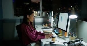 Vista lateral do executivo fêmea caucasiano novo que trabalha no computador na mesa em um escritório moderno 4k filme