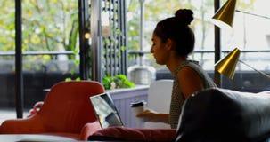 Vista lateral do executivo fêmea caucasiano novo que trabalha no portátil e no café bebendo no escritório moderno filme