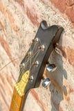 Vista lateral do headstock da guitarra acústica da Seis-corda no fundo da parede imagem de stock royalty free