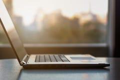 Vista lateral do laptop do escritório na tabela da mesa sobre com cidade b imagens de stock