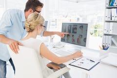 Vista lateral dos editores de fotos que trabalham no computador Fotografia de Stock
