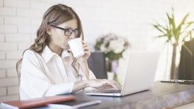Vista lateral dos vidros vestindo de uma mulher bonita nova que datilografam em seu portátil no escritório Tiro médio Imagem de Stock