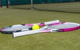 Vista lateral em raquetes de tênis com uma bola de tênis em uma grama verde Fotos de Stock Royalty Free