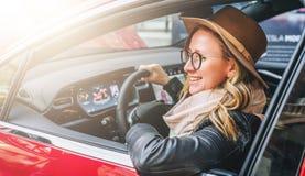 Vista lateral, fim acima A mulher de sorriso nova nos vidros e no chapéu senta-se roda atrás dentro o carro vermelho Viagem, cara Fotos de Stock Royalty Free