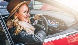 Vista lateral, fim acima A mulher de sorriso nova nos vidros e no chapéu senta-se roda atrás dentro o carro vermelho Viagem, cara Imagens de Stock