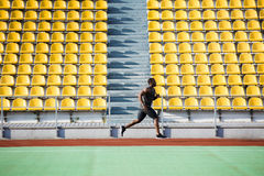Vista lateral integral de un deportista que corre en pista Fotos de archivo libres de regalías