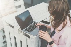 Vista lateral La empresaria joven se está sentando en la tabla en el café de la calle, café de consumición, ordenador portátil de Fotografía de archivo libre de regalías