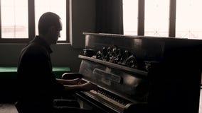 Vista lateral Pianista que juega el piano del vintage en interior pasado de moda almacen de metraje de vídeo