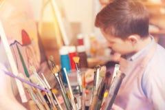 Vista lateral sobre adolescente en clase de la pintura Fotografía de archivo libre de regalías