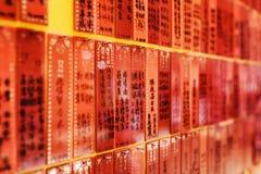 Vista lateral sobre las placas rojas con las inscripciones en la pared del templo adentro imagen de archivo