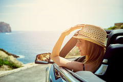 Vista lateral sobre mujer sonriente en coche convertible fotos de archivo