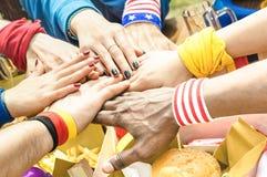 Vista lateral superior de manos multirraciales de los amigos del partidario del fútbol fotografía de archivo libre de regalías